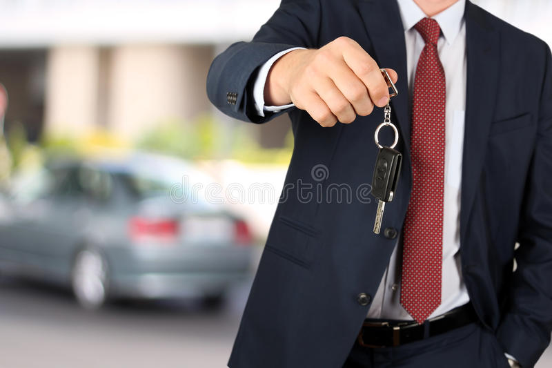 Successful businessman offering a car key. Close-up of driver`s hand showing key.  royalty free stock images