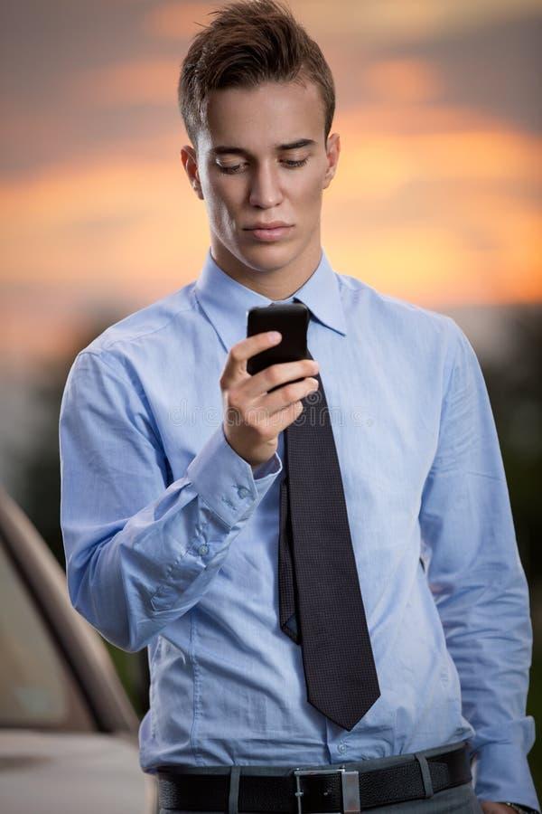 Successful businessman on phone. Sunset on back stock image