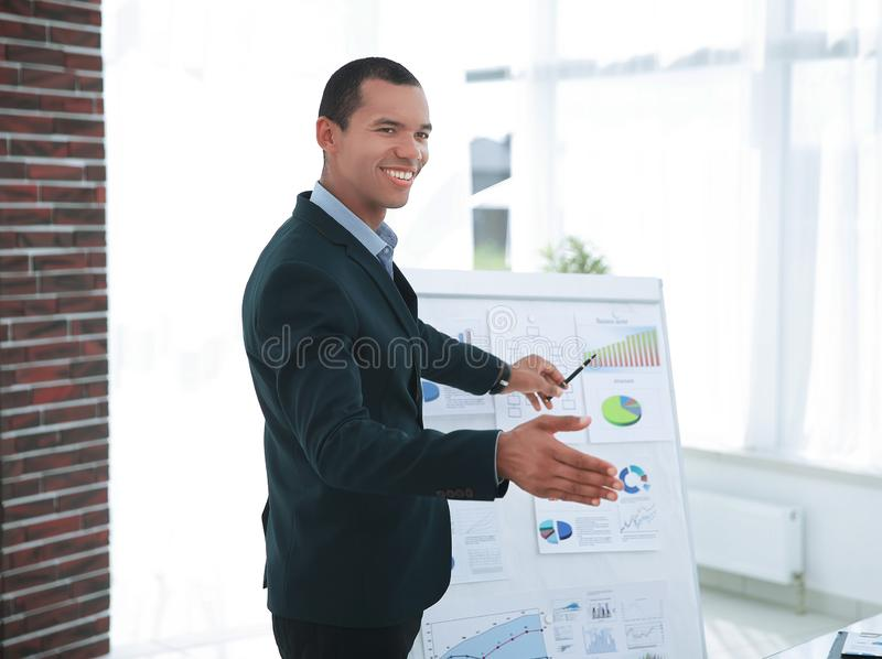 Successful businessman pointing to a flip chart with the financial information. stock photography