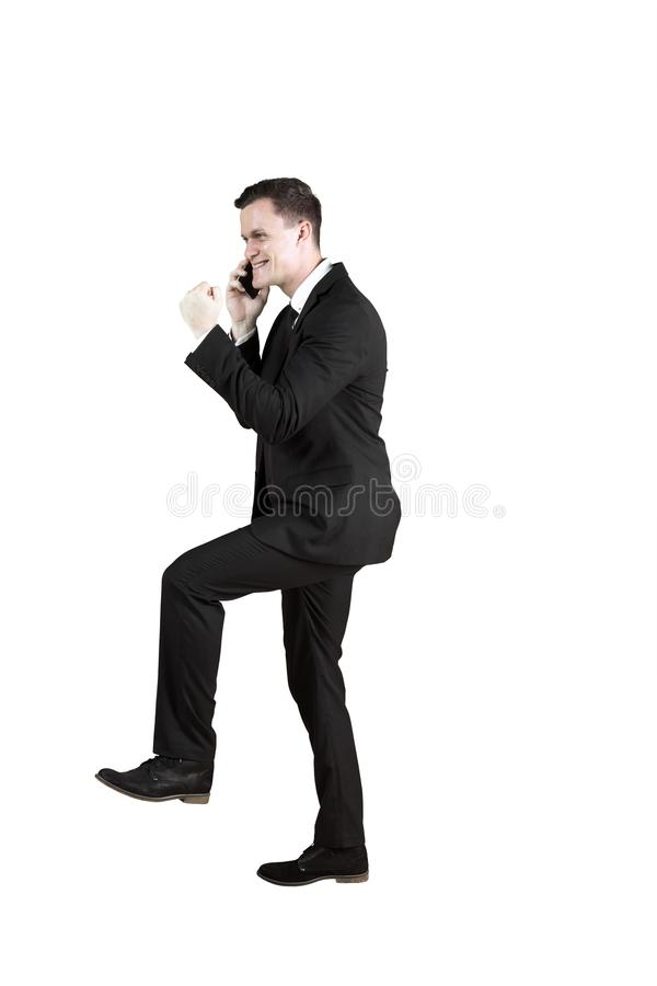 Successful businessman with phone on studio. Successful businessman poses stepping upward while talking on the mobile phone, isolated on white background stock image