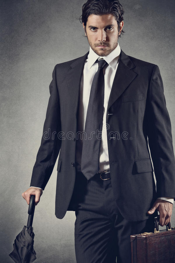 Successful businessman posing with umbrella stock photography
