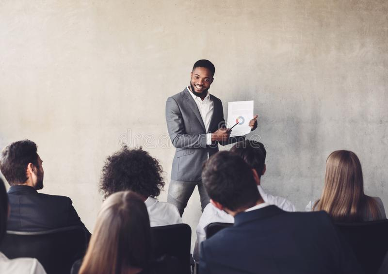 Successful businessman presenting diagrams to colleagues on training royalty free stock photo
