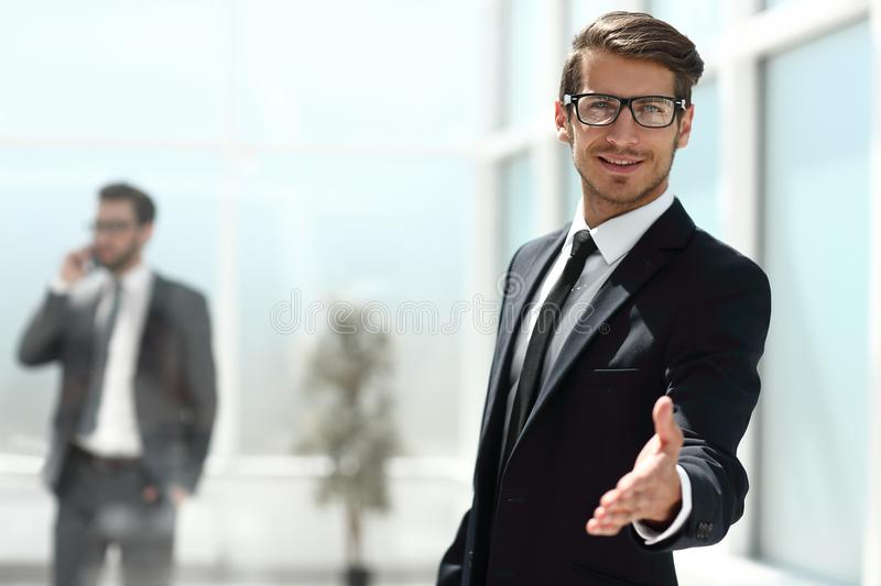 Successful businessman reaching out for a handshake. Photo with copy space stock photo