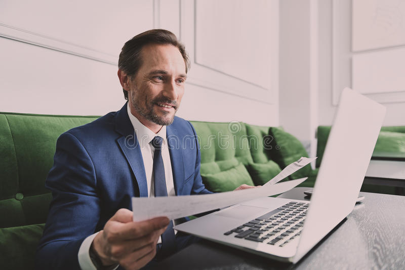 Successful businessman reading documents while using computer. Confident man in suit is checking necessary information from papers and comparing it with data on royalty free stock photo