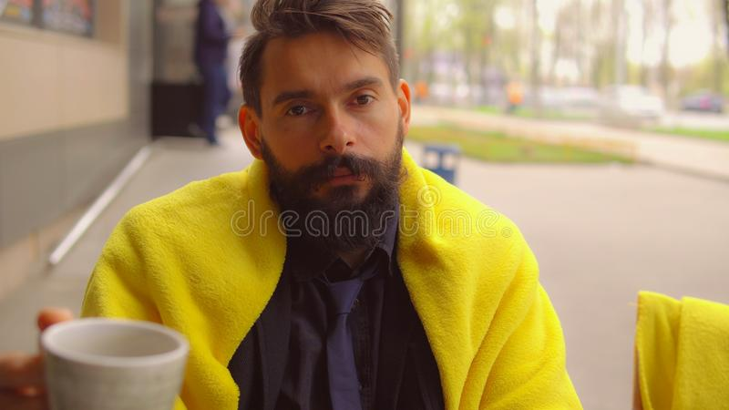 Successful businessman relish drink outdoors. Handsome caucasian man sitting in outdoor cafe in autumn season. portrait hipster guy enjoy coffee looking at stock photos