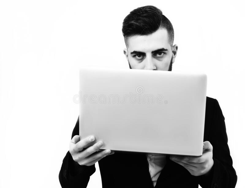 Successful businessman with serious look holds white laptop stock photo