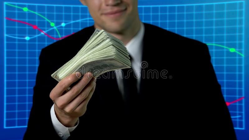 Successful businessman showing bunch of dollars, market graphics on background. Stock photo stock image