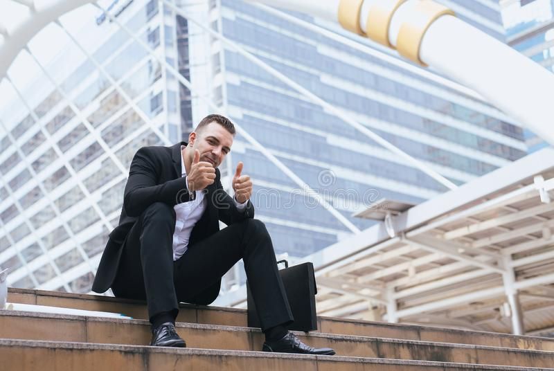 Successful businessman showing his thumb up and smiling stock photos