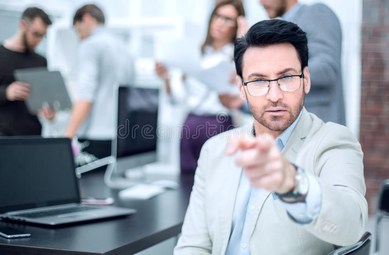 Successful businessman sitting at his Desk and pointing at you royalty free stock photo