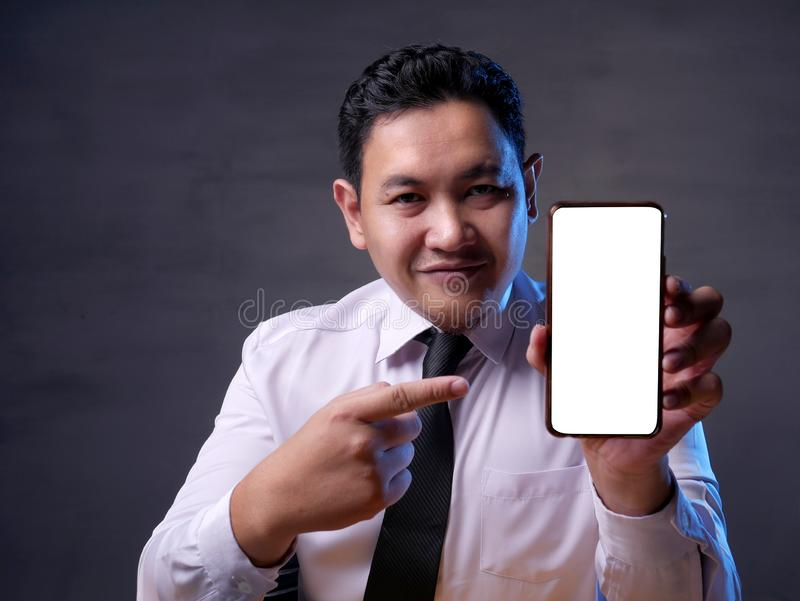 Successful Businessman with Smart Phone Mockup. Close up image of smart phone mockup, happy successful businessman holding phone with white screen template, copy royalty free stock photo