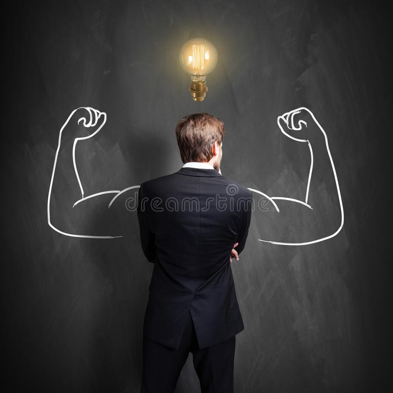 Successful businessman standing in front of a blackboard with a bright lightbulb over his head royalty free stock photos