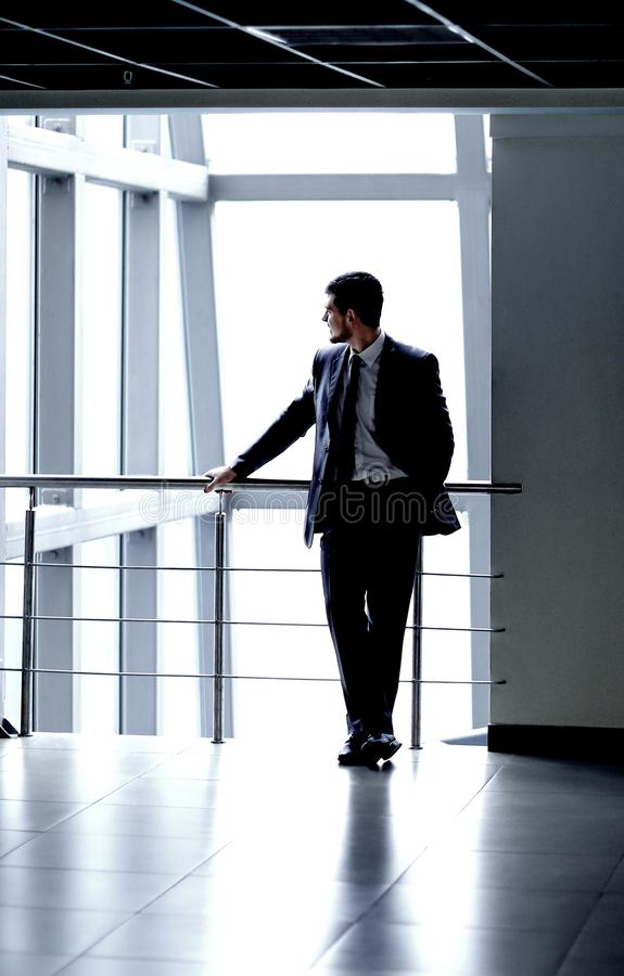 Successful businessman standing in the lobby of a modern office royalty free stock photography