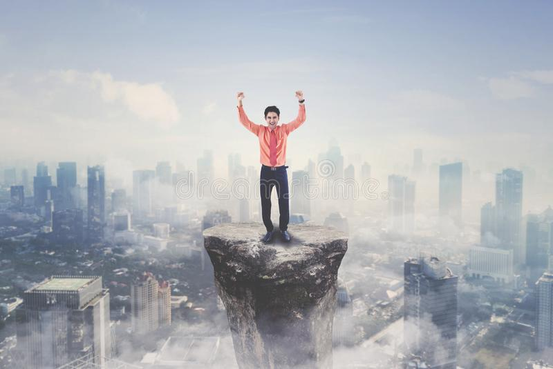Successful businessman standing on the mountain. Arabian businessman expressing his success by lifting hands while standing on the mountain with modern city stock image