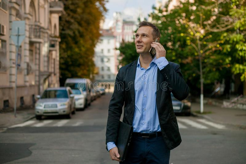 Successful businessman in suit with laptop in the city royalty free stock image