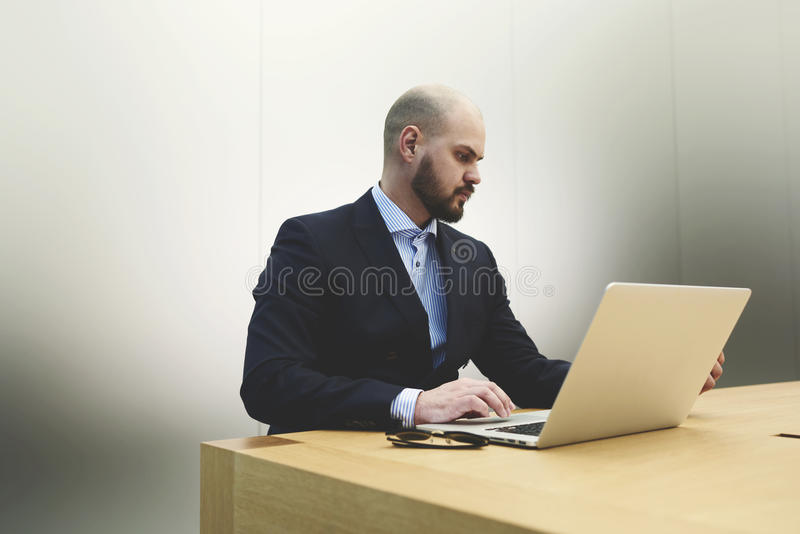 Successful businessman in suit is searching on net-book needed information for conference. Young male skilled financier is performing economic analysis of royalty free stock image