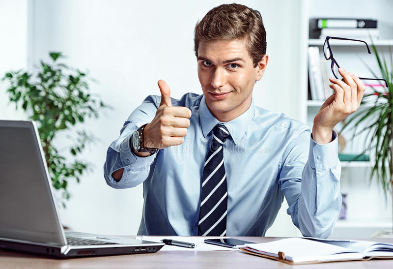 Successful businessman takes off his glasses and showing thumb up royalty free stock photo