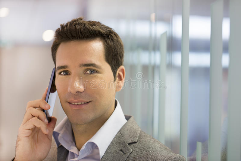Successful businessman talking on cell phone, looking camera royalty free stock photos