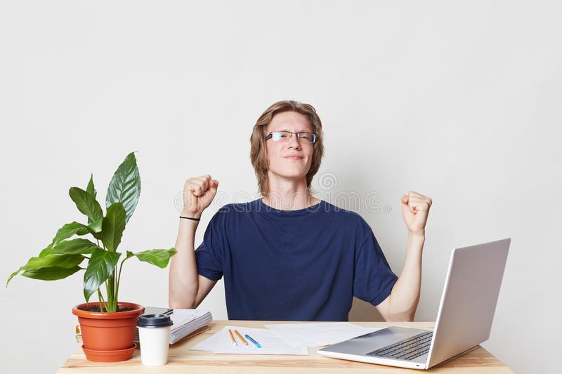 Successful businessman at work place clenches fists, celebrates his victory and triumph, being glad to sign contract with partners stock image