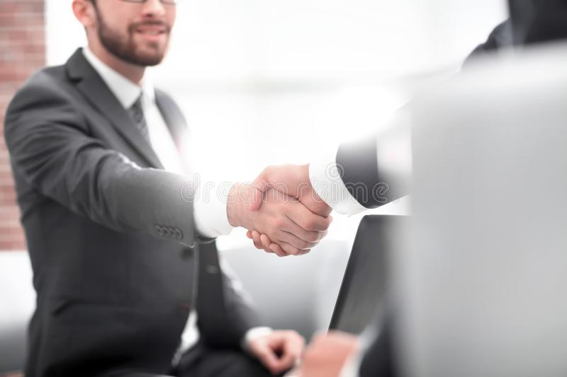Confident businessman shaking hands at officce stock images