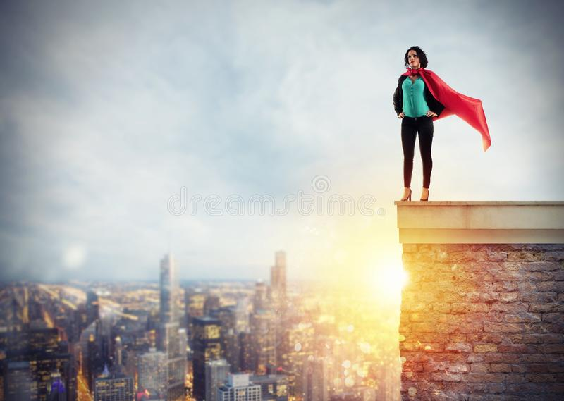 Successful businesswoman acts like a super hero above the roof of a building. Concept of determination and success stock images
