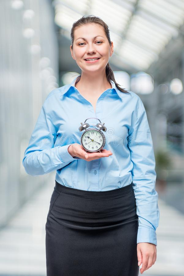 Successful businesswoman with an alarm clock in hands stock photos