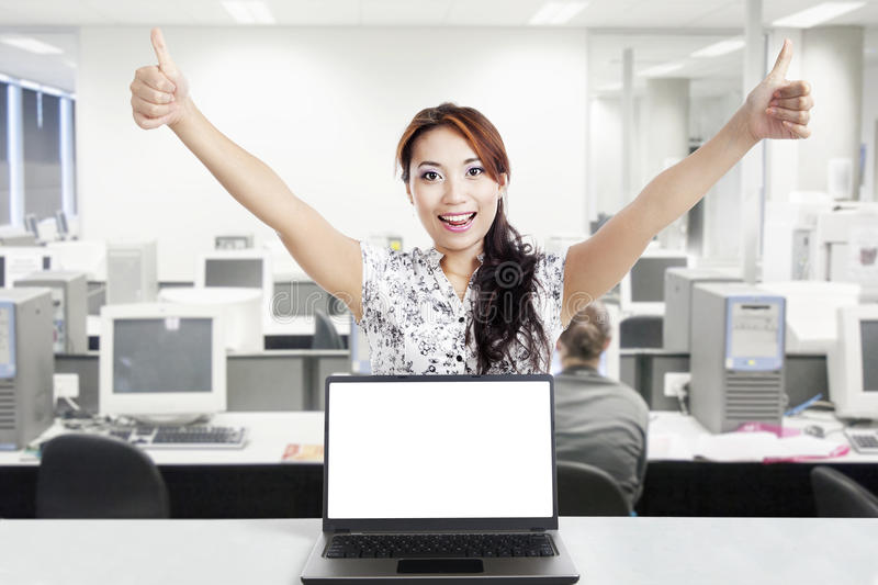 Successful businesswoman and blank monitor. Young businesswoman hold thumbs up behind a blank monitor in the office stock images