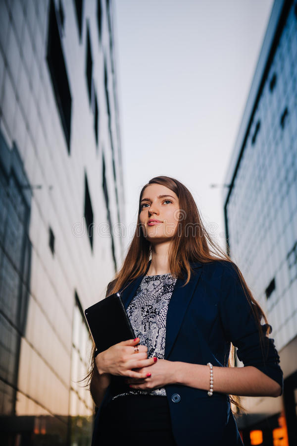 Successful businesswoman or entrepreneur taking notes and talking on cellphone while walking outdoor. City business woman. Working stock images