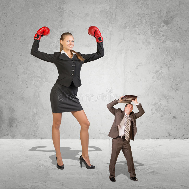 Successful businesswoman flexing her powers. Businesswoman flexing her powers in conceptual image of giant business women wearing boxing gloves towering over stock image