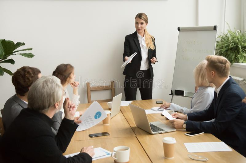 Businesswoman talking to business team answering questions at gr royalty free stock images