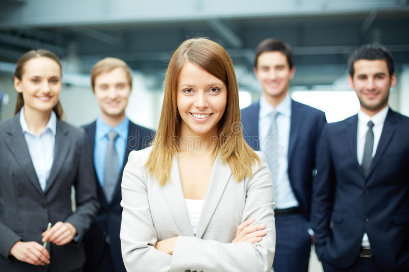 Successful businesswoman. Group of friendly businesspeople with happy female leader in front stock photography