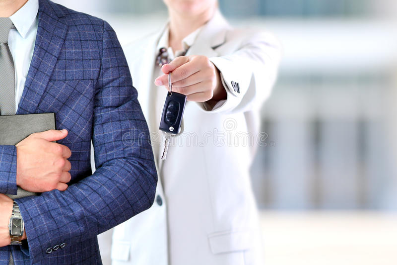 Successful businesswoman offering a car key.Business man holding documents behind. Car rental stock image