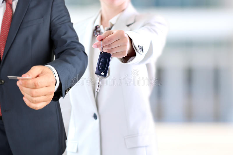 Successful businesswoman offering a car key.Business man offering a business card. Successful businesswoman offering a car key.Business man offering a business stock photos