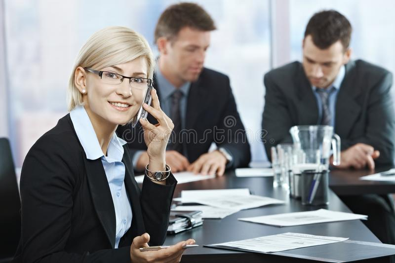 Businesswoman on phone at meeting. Successful businesswoman smiling talking on phone at meeting with businessmen in background stock photography