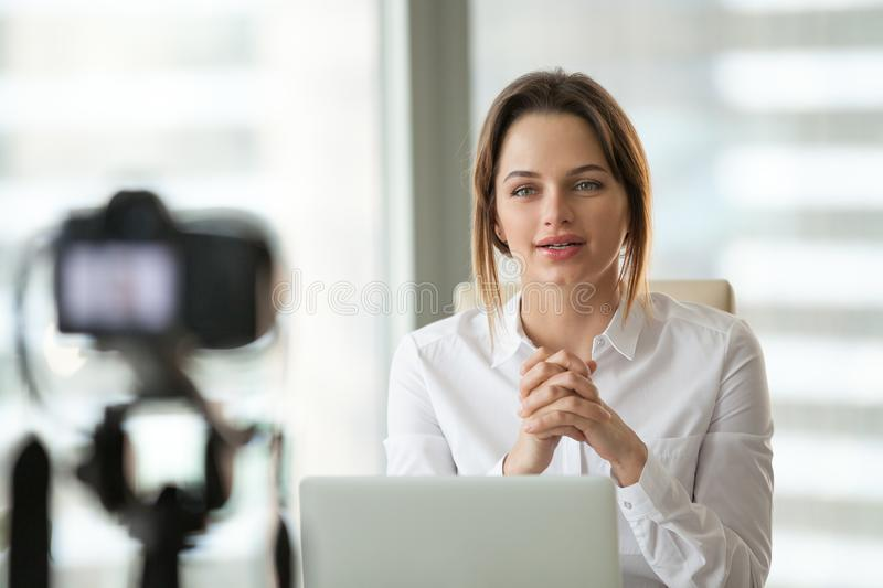 Successful businesswoman vlogger or coach talking to camera film royalty free stock photo