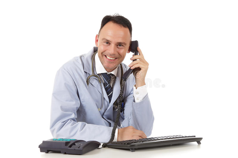 Successful caucasian man docto, office. Smiling Middle aged successful caucasian man doctor in the office at his desk with keyboard and telephone. Studio shot stock photo