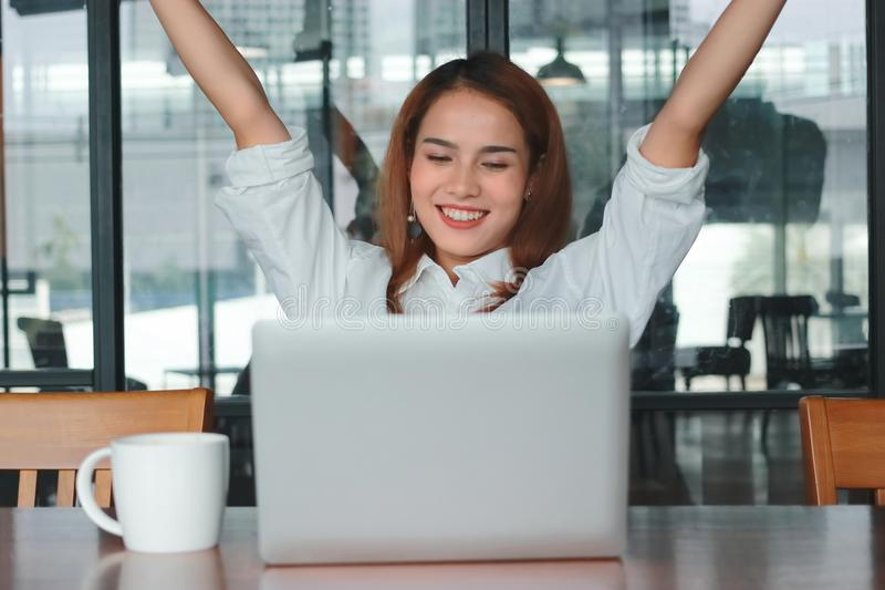 Successful cheerful young Asian businesswoman with laptop raising hands in office. Thinking and thoughtful business concept. royalty free stock photos