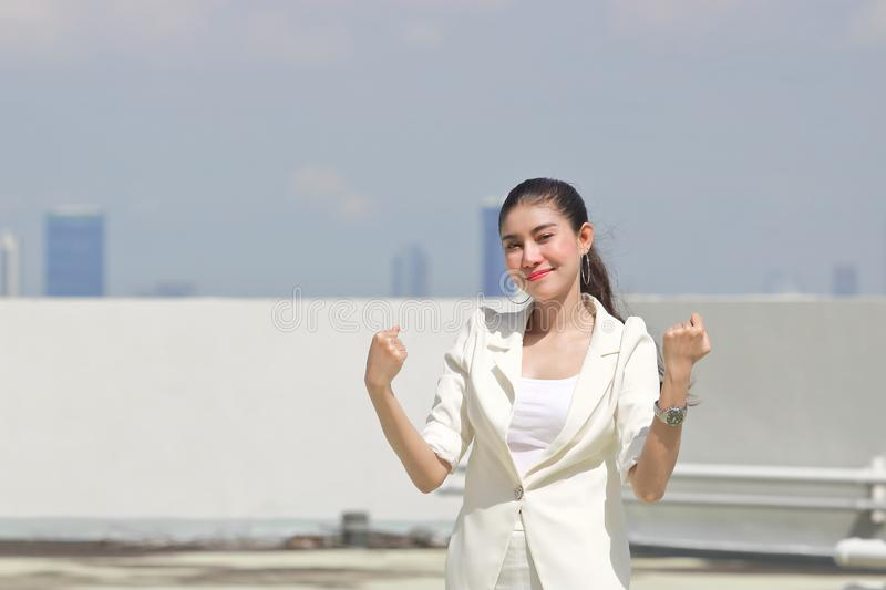 Successful cheerful young Asian businesswoman raising hands outside office. Thinking and thoughtful business concept stock photos