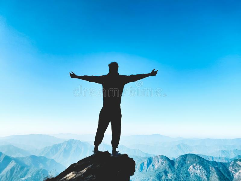 Successful Climb. A silhouette of an ecstatic person after a successful climb to the summit of a Himalayan mountain with beautiful layered hills and bright blue royalty free stock images