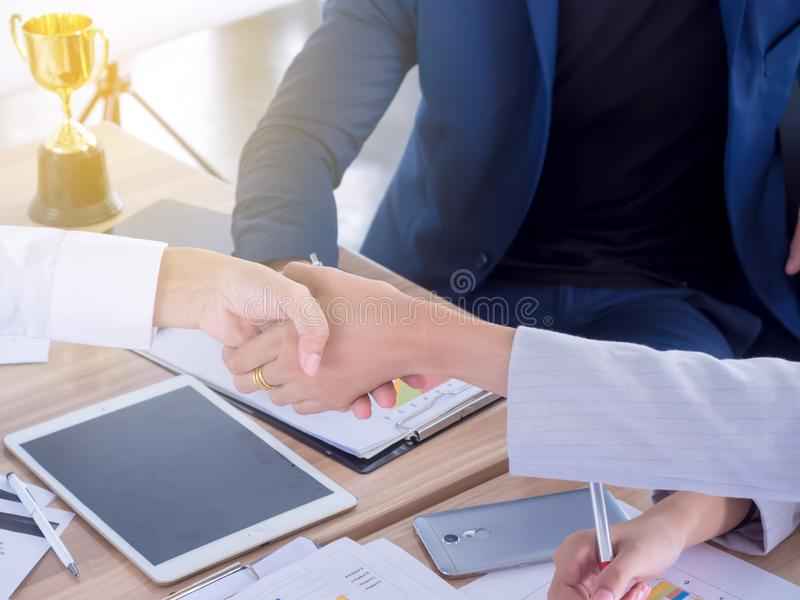 Successful Close-up of two businesswomen shaking hands with smile while sitting at the business meeting with their coworkers stock photography