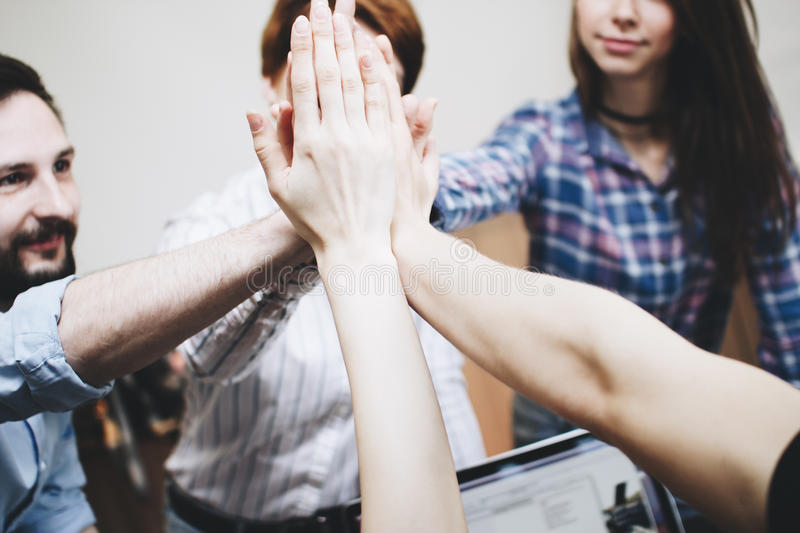 Successful and cohesive team of people make High Five stock images