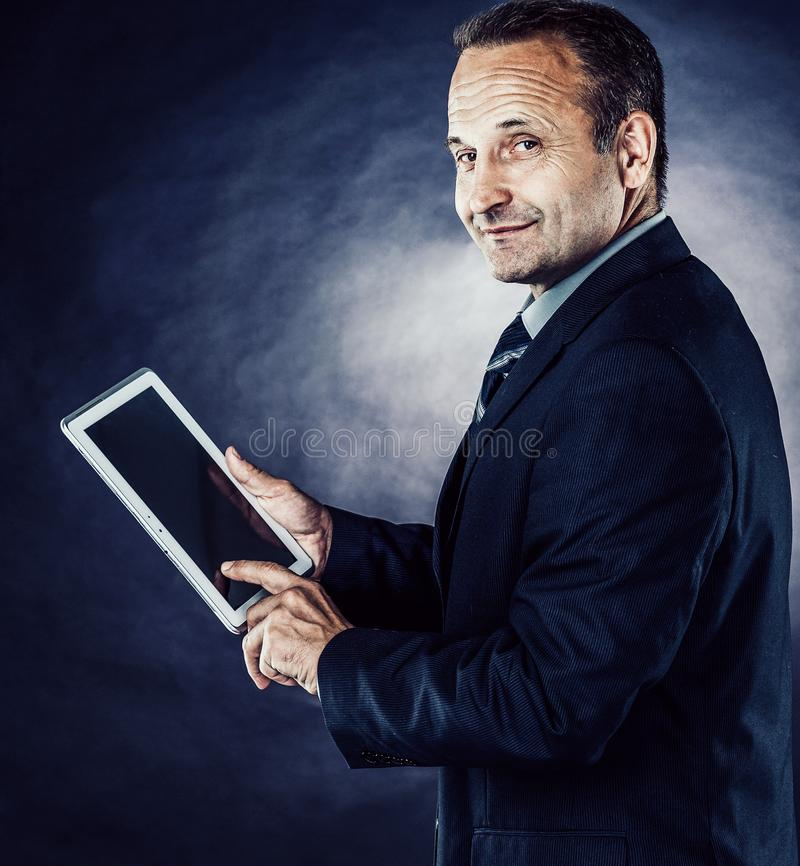 A successful, confident businessman examines a contract on a tab royalty free stock image