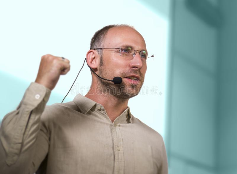 Successful and confident businessman with headset speaking at corporate business coaching and training auditorium conference room. Young successful and confident stock photo