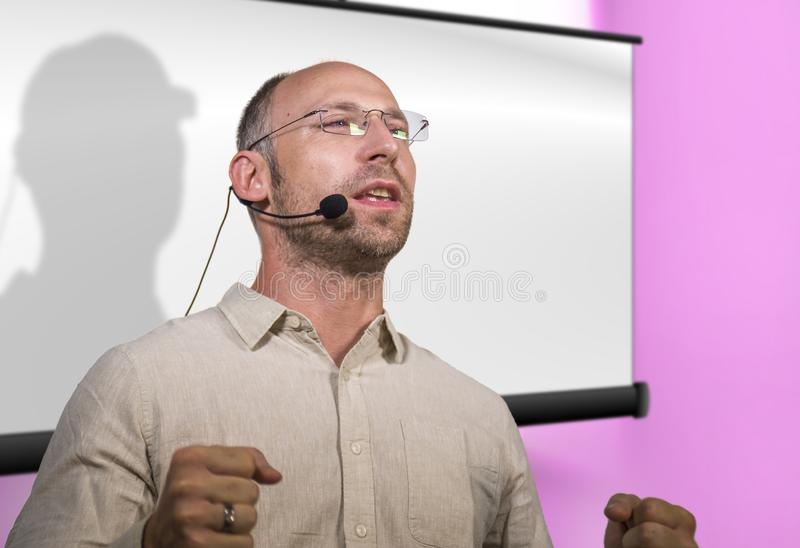 Successful and confident businessman with headset speaking at corporate business coaching and training auditorium conference room. Young successful and confident stock images
