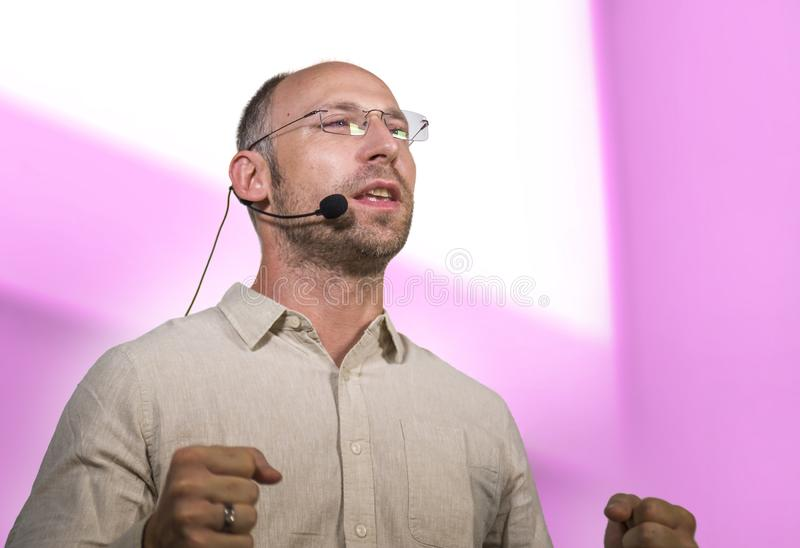 Successful and confident businessman with headset speaking at corporate business coaching and training auditorium conference room. Young successful and confident royalty free stock photos