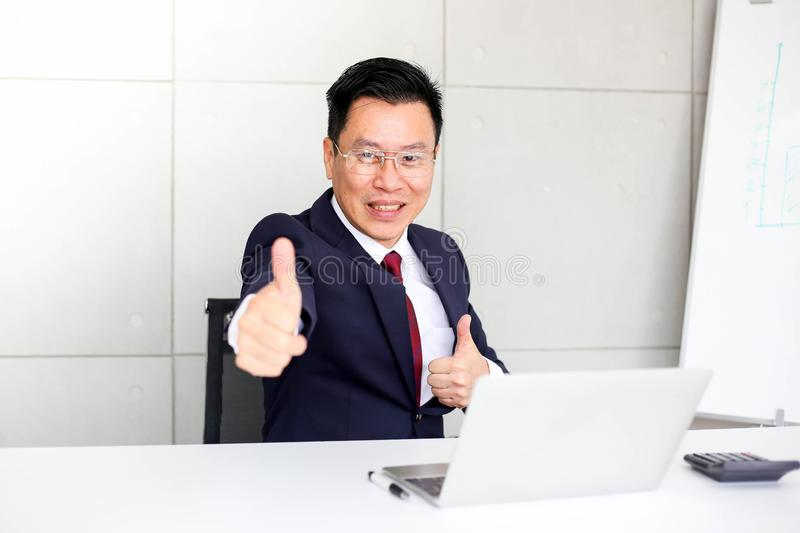Successful confident businessman ,showing thumbs up or like sitting at office desk,success, good idea, great job business concept royalty free stock images
