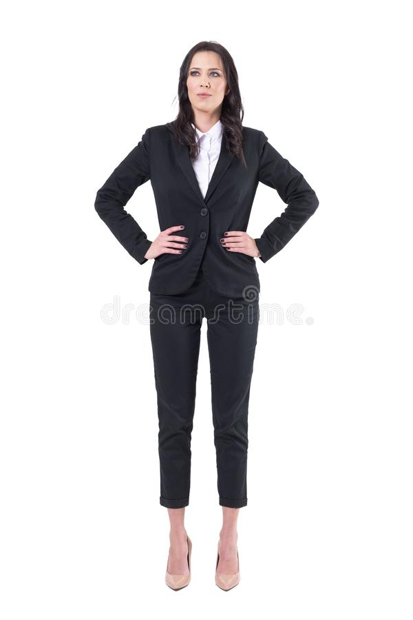 Successful confident businesswoman manager standing with arms on hips looking up royalty free stock photo