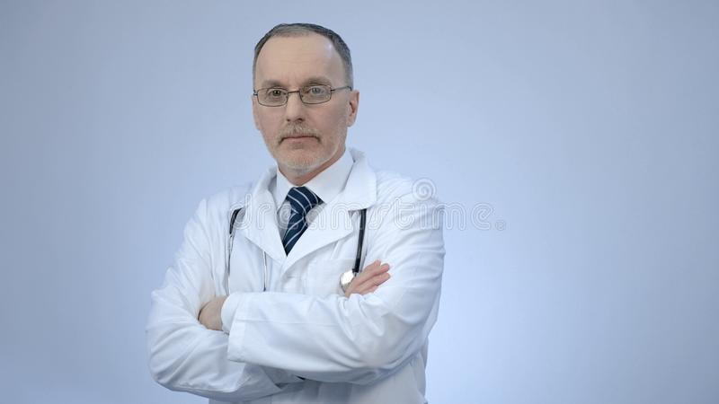 Successful confident doctor looking at camera with folded arms, clinic services stock image