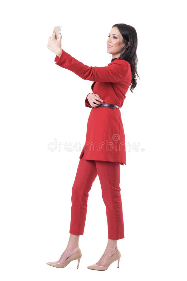 Successful confident elegant business woman taking selfie with smart phone. Side view. royalty free stock images