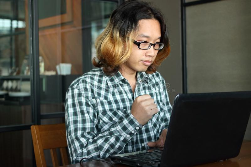 Successful and confident young Asian hipster with casual clothes working with laptop for his job in workplace of office. stock photos