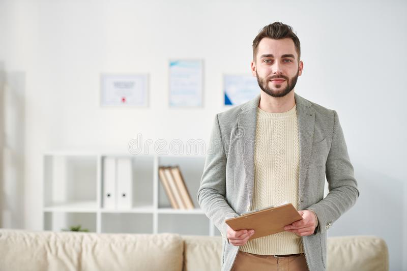 Successful counselor. Handsome young confident man in smart casual standing in front of camera inside his office during work stock photos
